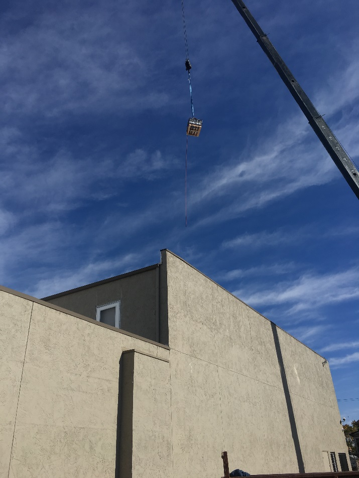 crane moving equipment to building top